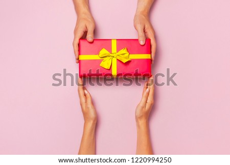 Top view of male and female hands holding red gift box with golden ribbon on pink background Flat lay. Present for birthday, valentine day, Christmas, New Year. Congratulations background copy space. #1220994250