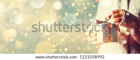 Shimmer background with snow, light bokeh. Woman hands opening gift box. Christmas, new year, birthday concept. Banner, copy space. Royalty-Free Stock Photo #1221038992