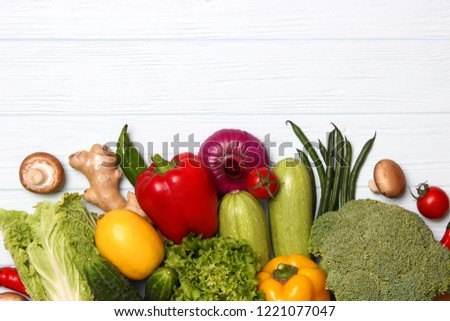 Different fresh vegetables on a wooden table top view. Proper and healthy food, diet, vegetarian. Cooking food, vegetable dishes. flat lay  #1221077047