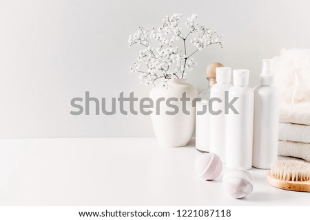 Soft light bathroom decor for advertising, design, cover, set of cosmetic bottles, bath accessories, white small flowers in vase, towel on white wooden shelf. mock up,copy space  #1221087118
