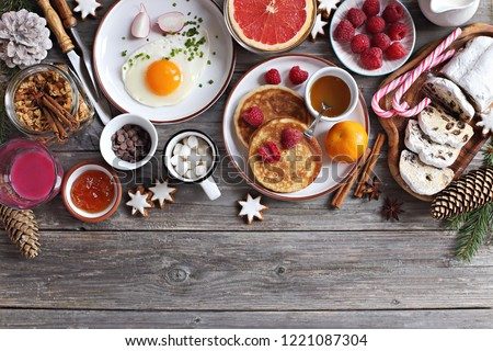 Christmas brunch or breakfast table. Festive brunch set, meal variety with fried egg, appetizers platter, croissant, granola, smoothy and traditional sweets . Overhead view #1221087304