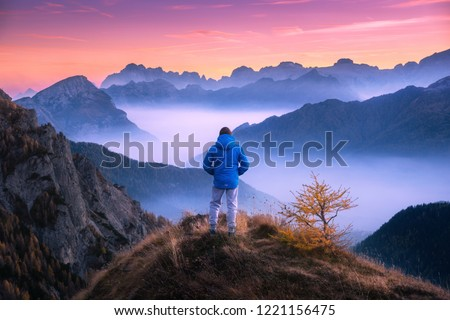 Sporty man on the mountain peak looking on mountain valley with low clouds at colorful sunset in autumn in Dolomites. Landscape with traveler, foggy hills, forest in fall, amazing sky at dusk in Alps #1221156475