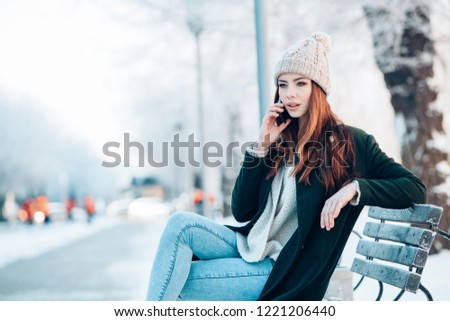 Young  woman smiling with smart phone and winter landscape .