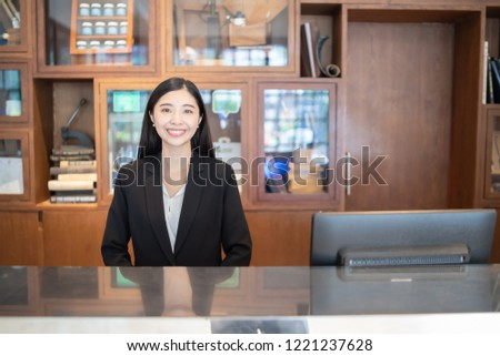 Welcome to the hotel,Happy young Asian woman hotel receptionist worker smiling standing at a Modern luxury  reception counter waiting for guests getting key card in hotel inn motel, lodge, hostel, #1221237628