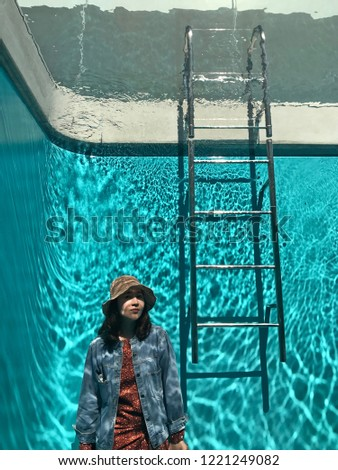 Kanazawa,Japan-Circa September 2018: Young woman tourist stands next to a climbing ladder for photography in the swimming pool room that creates the illusion of being underwater whilst remain dry. #1221249082