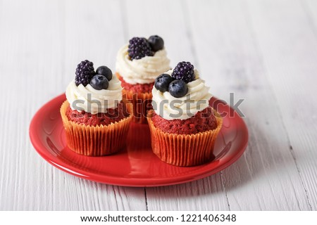 Tasty red velvet cupcakes with blueberry and blackberry on wooden table. #1221406348