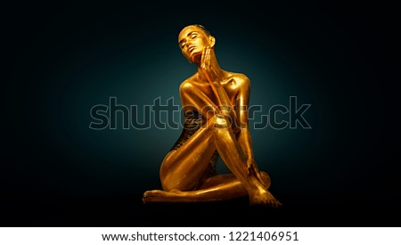 High Fashion model girl with bright golden sparkles on her body posing, full length portrait of beautiful sexy woman with glowing body skin. Art design make up. Glitter gold sequins on skin body art #1221406951