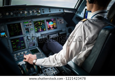 Pilot's hand accelerating on the throttle in  a commercial airliner airplane flight cockpit during takeoff #1221423478