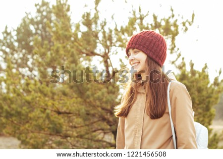 A young girl smiles against the background of the forest. The concept of travel and adventure. copy space. #1221456508