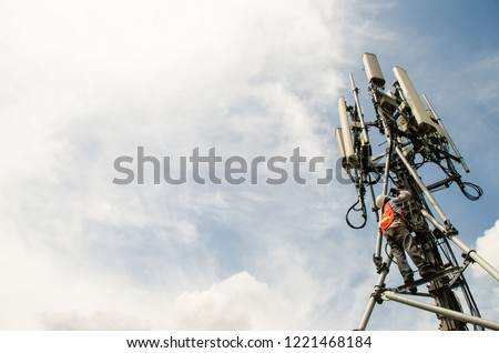 Telecommunication engineer working on high tower,Risk work of high work,Technician working with safety equipment on tower,Sky background.Technician take picture while working on tower. #1221468184