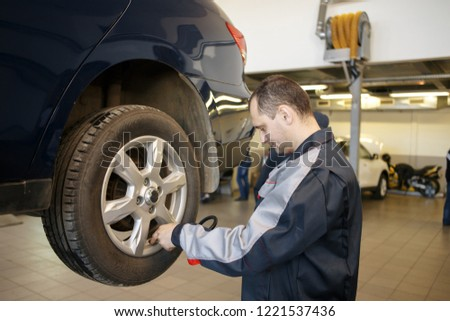 Hand of car mechanic with wrench. Auto repair garage. #1221537436