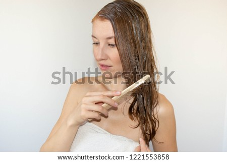 beautiful red-haired girl in a white towel combs wet hair masked on a white background, spa #1221553858