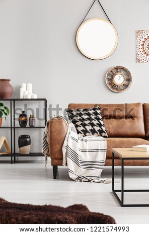 Vertical view of warm ethno living room with leather couch with patterned pillow and mirror and clock on beige wall, real photo #1221574993