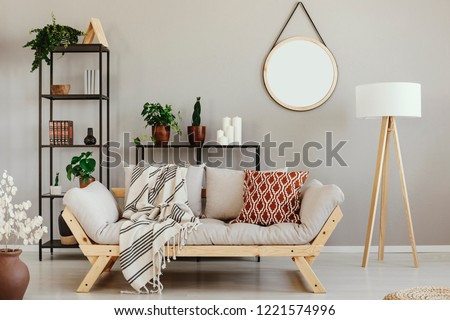 Green plants in pots, candles and books on metal shelves in beige scandinavian living room with comfortable settee, lamp and mirror on the wall #1221574996