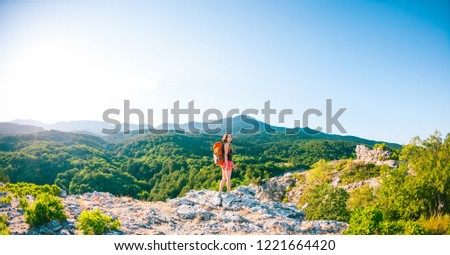 Girl at the top of the mountain. A woman with a backpack walks along a mountain path. Climb to the top. Travel to picturesque places. Tourist against the sky and the sea. #1221664420