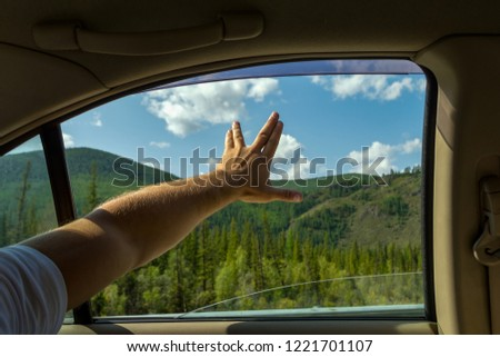 The man's arm, covered with hair, is open, showing the sign of startrek by the fingers spread background the blue sky with white clouds and green coniferous tree