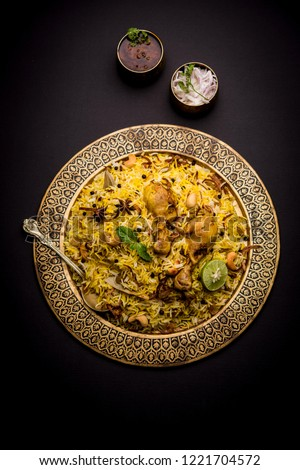 Delicious spicy chicken biryani in bowl over moody background, it's a popular Indian and Pakistani food. #1221704572