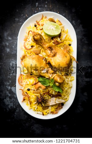 Delicious spicy chicken biryani in bowl over moody background, it's a popular Indian and Pakistani food. #1221704731