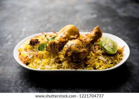 Delicious spicy chicken biryani in bowl over moody background, it's a popular Indian and Pakistani food. #1221704737