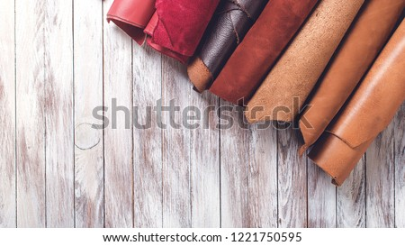 Multi colored leather in rolls. Flat lay. Rolls of natural color leather. Materials for leather craft. Copy space. Top view. Handmade craft. Different samples of leather on wooden table #1221750595