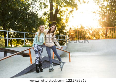 Two smiling young girls on on roller skates spending time together at the skate park #1221758563