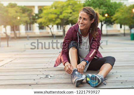 Mature fitness woman tie shoelaces on road. Cheerful runner sitting on floor on city streets with mobile and earphones wearing sport shoes. Active latin woman tying shoe lace before running. #1221793927