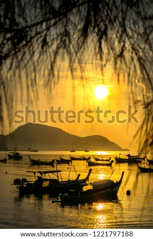 Boat sailing along its journey against a vivid colorful sunset in formation against an orange and yellow color filled sky sunset fantasy with a silhouette in Phuket ,Thailand. #1221797188