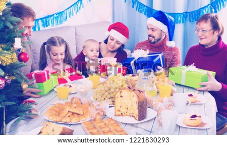 Large cheerful positive smiling family exchanging gifts during Christmas dinner #1221830293