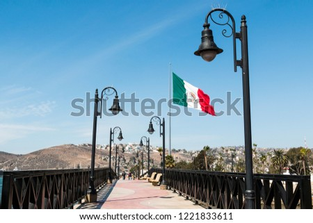 Pedestrian bridge leading to the marina and waterfront shops in Ensenada, Mexico, with a giant flag of Mexico. #1221833611