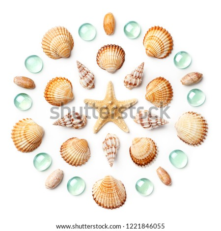 Pattern in the form of a circle made of shells, starfish and green glass beads isolated on white background. Flat lay, top view #1221846055