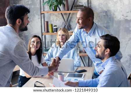 New business partners. Young modern colleagues in smart casual wear shaking hands and smiling while sitting in the creative office #1221849310