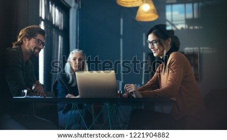 Business professionals sitting around table and looking at laptop. Asian female executive giving a presentation over laptop to colleagues at office. #1221904882