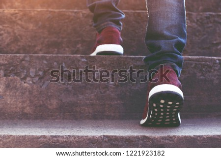 stairway. Close up legs jeans and shoes sneakers red of young hipster man One person walking stepping going up the stairs in modern city, go up staircase, success, grow up. Sunshine in the morning. Royalty-Free Stock Photo #1221923182
