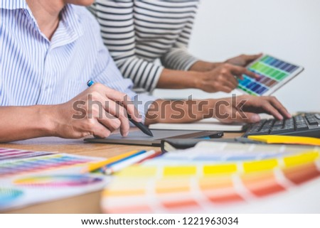 Young creative team having a meeting in creative office, Architectural drawing with work tools and accessories, Color swatch samples chart for selection coloring. #1221963034