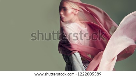 A beautiful young tender girl in a chiffon dress is covered with a drapery made of thin fabric that develops in the wind.fashion, beauty, makeup, cosmetics, beauty salon, style, personal care, posture #1222005589