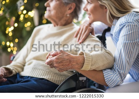 A senior woman in wheelchair with a health visitor at home at Christmas time. #1222015330