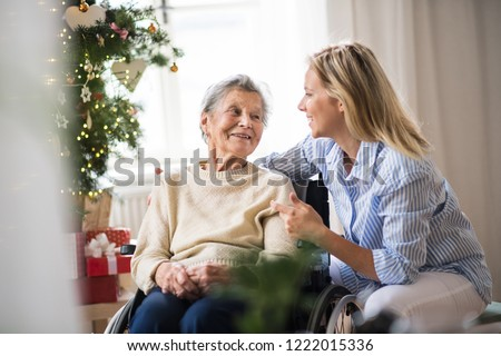 A senior woman in wheelchair with a health visitor at home at Christmas time. #1222015336