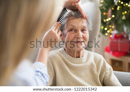 A health visitor combing hair of senior woman at home at Christmas time. #1222015342
