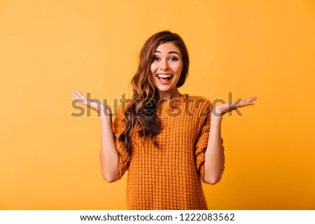 Spectacular funny girl expressing positive emotions on yellow background. Studio portrait of magnificent long-haired woman in elegant sweater.