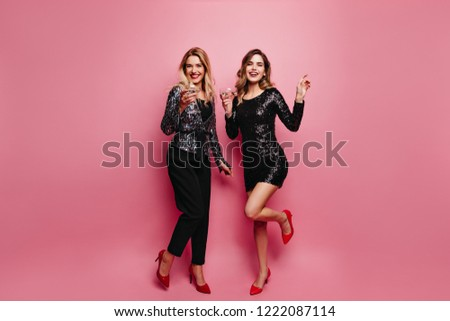 Full-length portrait of glad woman in sparkle dress chilling at party. Jocund european girl in black pants posing on rosy background. #1222087114
