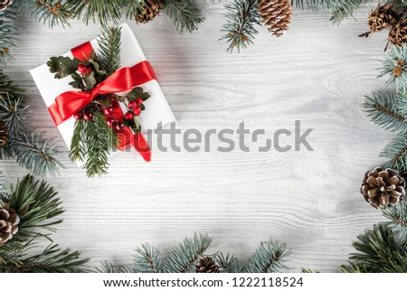 Creative frame made of Christmas fir branches on white wooden background with gift box, pine cones. Xmas and New Year theme. Flat lay, top view #1222118524