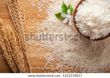 Top view of jasmine rice in a bowl on dark wooden table with rice plants, jasmine flower, ear of rices with jasmine rice in a bowl , rice scatter on the floor. #1222150837
