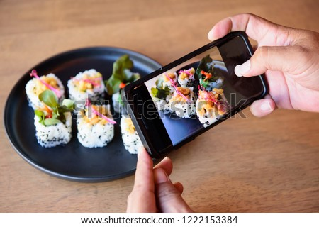Shooting before eating, new trend for new generation. Sushi in Japaneese restuarant.
