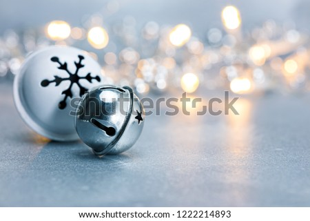 festive christmas jingle bells on grey background with blurred garland lights. macro view #1222214893