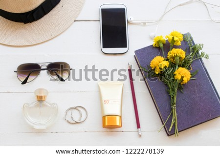 natural sunscreen spf50 ,hat ,perfume ,mobile phone ,earring ,booklets and sunglasses accessories of lifestyle woman relax with marigold flowers arrangement on background wooden white #1222278139