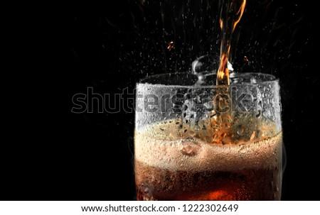 Soft drink glass with ice splash on dark background. #1222302649