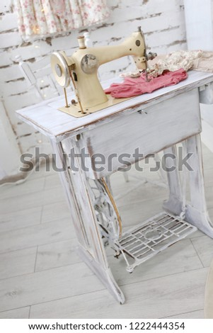 old vintage beige sewing machine in atelier with white brick walls #1222444354