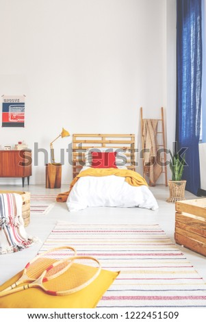 Tennis paddles on yellow cushion in bedroom interior with plant and lamp next to bed. Real photo #1222451509