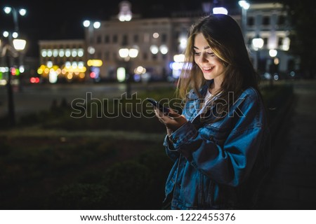 Young Caucasian woman texting cell phone in city at night