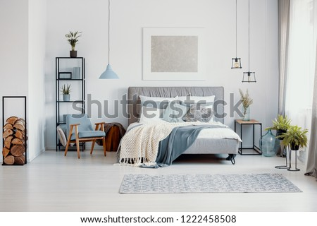 Silver painting above bed with knitted blanket in white bedroom interior with blue armchair. Real photo #1222458508